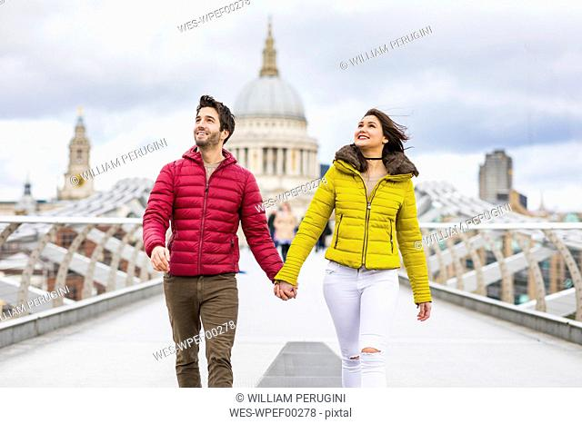 UK, London, young couple walking hand in hand on bridge in front of St Pauls Cathedral