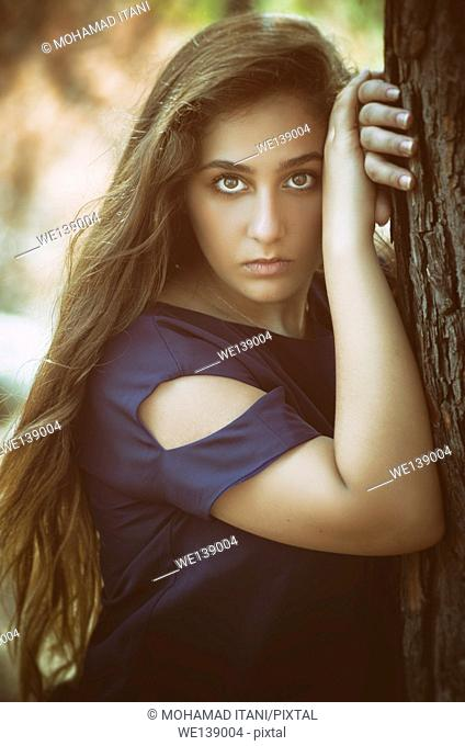Beautiful teenage girl leaning aginst the tree staring