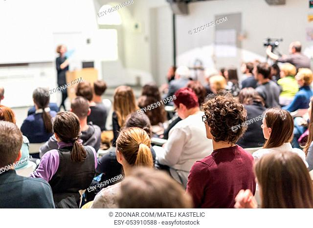 Business and entrepreneurship symposium. Female speaker giving a talk at business meeting. Audience in conference hall. Rear view of unrecognized participant in...