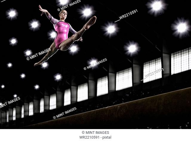 A young woman gymnast performing on the beam, balancing on a narrow piece of apparatus