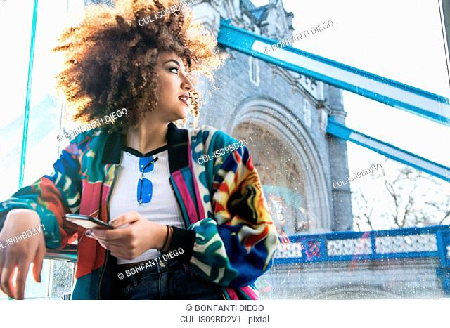Young girl outdoors, holding smartphone, looking away, Tower Bridge in background, London, England, UK
