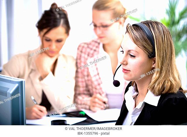 Young woman using a headset in an office