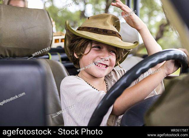 Smiling 6 year old boy in the driving seat of a safari vehicle