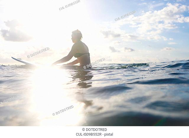 Woman straddling surfboard in sunlit sea, Nosara, Guanacaste Province, Costa Rica