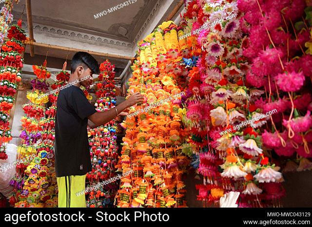 People arrange and make garlands for sale made out of different kinds of plastic at a garland factory, ahead of the Durga Puja Festival in the outskirts of...