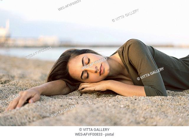Beautiful woman relaxing on the beach at sunset, portrait