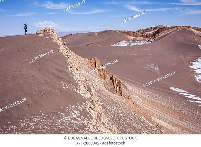 Trekking, in Valle de la Luna (Valley of the Moon ) and salt deposited on the ground, Atacama desert. Region de Antofagasta. Chile