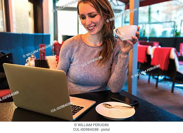 Mid adult woman in cafe looking at laptop
