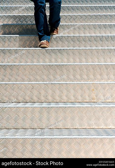 legs of a female clad in blue jeans and wearing brown shows walking down bright light clean aluminium stair steps
