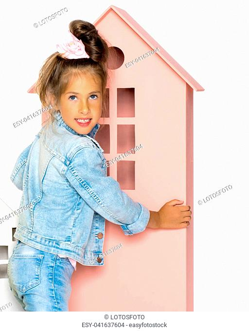 A cute little girl is playing with wooden houses. The concept of family happiness, play, creative development of the child