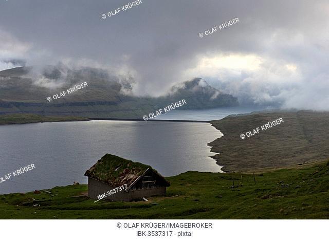 Hut at Eidisvatn lake, low clouds, Eysturoy, Faroe Islands, Denmark