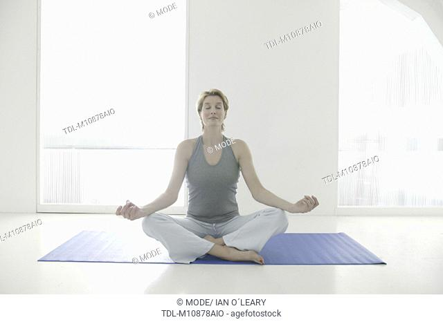 A woman sitting cross legged on a yoga mat meditating