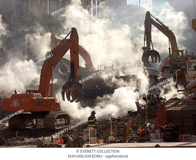Ground Zero still smolders as recovery operations continue a month after the terrorist attack. Oct. 10, 2001. Excavating equipment works in coordination with...