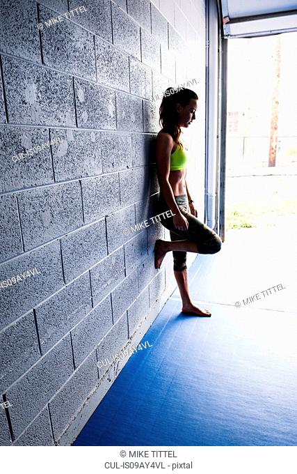Young female training leaning against gym wall