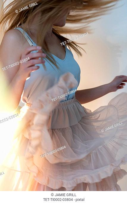 Young woman tossing her head while dancing