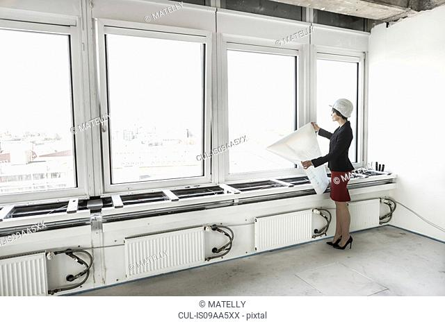 Businesswoman standing in empty unfinished office wearing hardhat and looking at plans