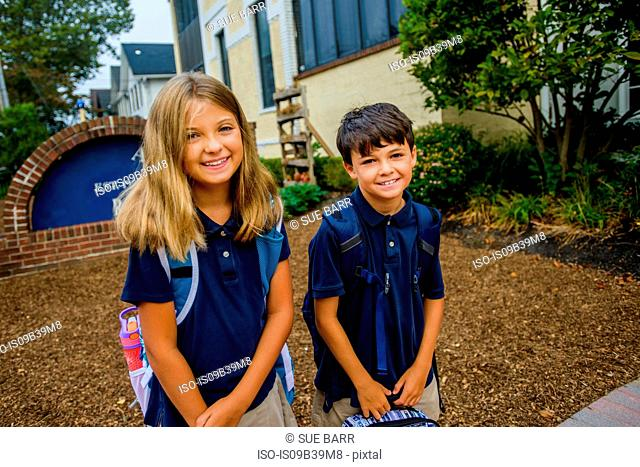 Portrait of male and female twins outside elementary school
