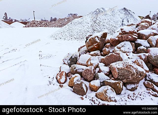 Rock and stone piles at a local road construction company in the winter. Ludington, Michigan, USA