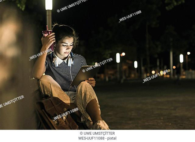 Young woman with smoothie sitting on bench at night using tablet