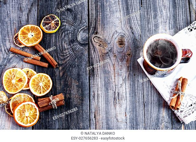 cup of hot coffee with orange slices on a gray wooden surface, empty space in the middle, top view