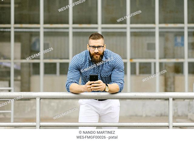 Portrait of bearded hipster businessman with smartphone leaning on railing