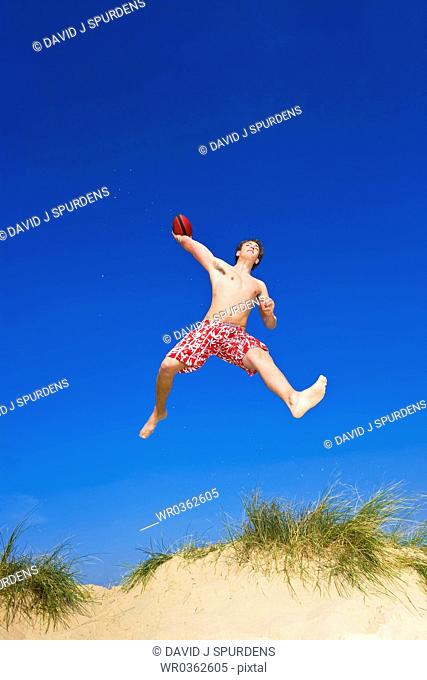 American Football palyer on Beach leaps high to pass ball