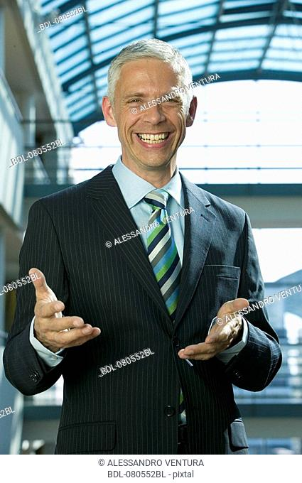 portrait of mature businessman making inviting gesture