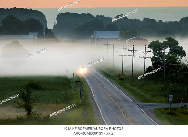Distant view of car driving in fog on road at sunrise, St. Anna, Wisconsin, USA