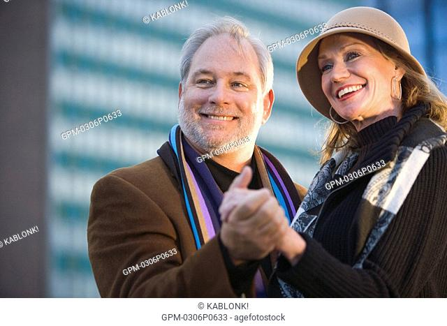Portrait of mature couple dancing on rooftop of modern downtown loft