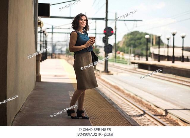 Mid adult woman waiting at train station, holding coffee cup
