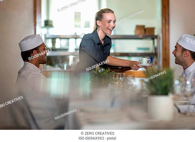 Waitress serving coffee to chefs at break time