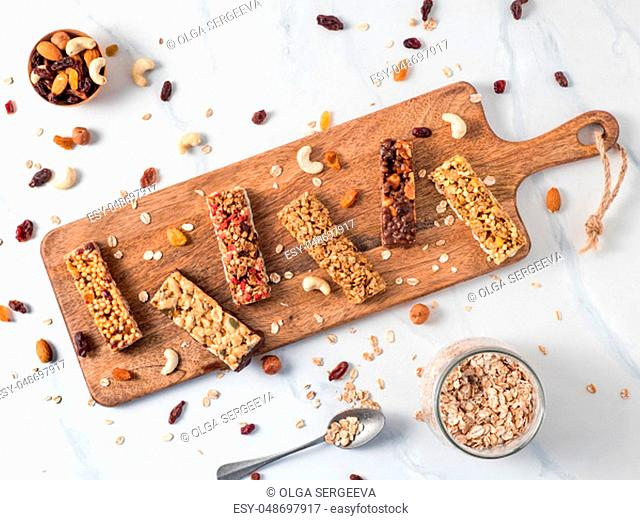 Granola bar with copy space. Set of different granola bars on cutting board over white marble table. Shallow DOF. Top view or flat lay