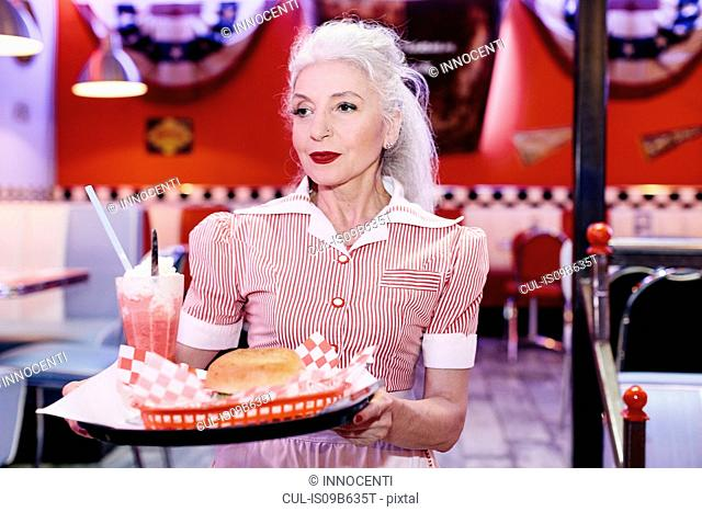 Mature female waitress serving burger in 1950's diner