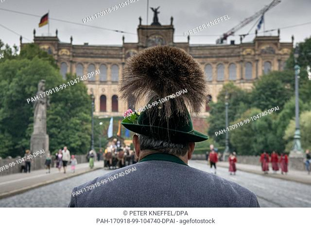 A man wearing traditional costume with a gamsbart on his felt hat outside the Bavarian Landtag parliament in Munich, Germany, 17 September 2017