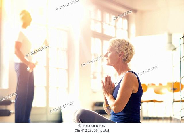 Older woman meditating on floor