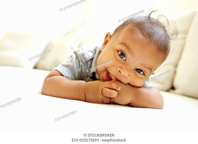 Smiling Baby Boy Lying On Tummy At Home