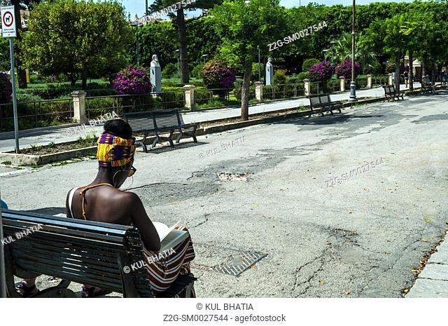 A black young woman reads a book sitting on a park bench on a warm, sunny day, in Noto, Sicily, Italy