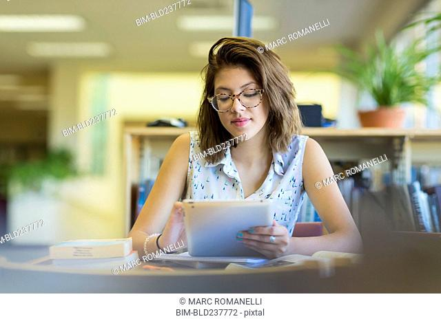 Mixed Race girl reading digital tablet in library
