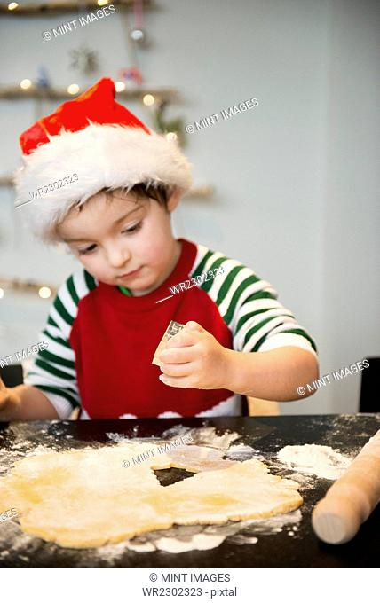 A boy in a Santa hat making Christmas biscuits, cutting out shapes