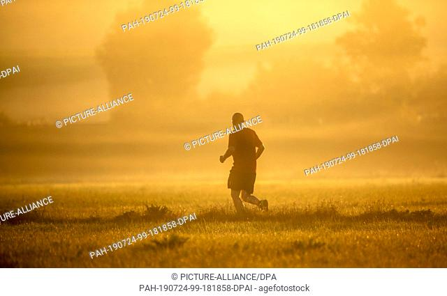 24 July 2019, Baden-Wuerttemberg, Unlingen: A jogger runs towards the sun shortly after sunrise. Temperatures of up to 38 degrees are predicted for the course...