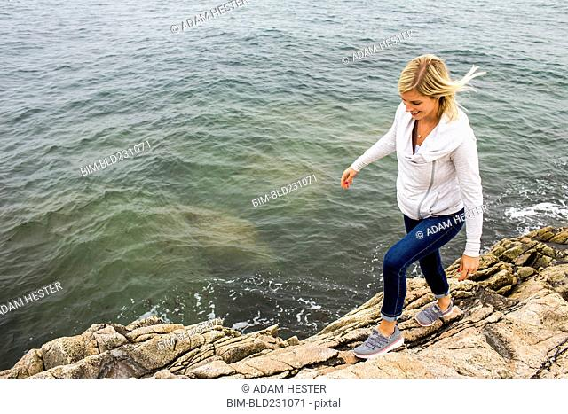 Caucasian woman walking on rocks at ocean