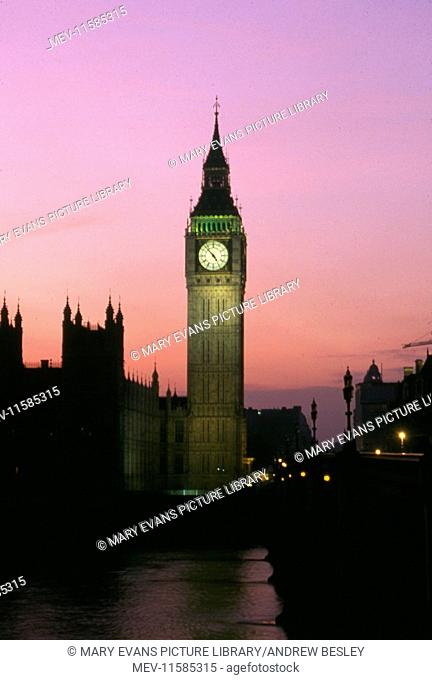 View of Big Ben and the Houses of Parliament alongside Westminster Bridge, London, in the early evening at sunset, with a pink and mauve sky