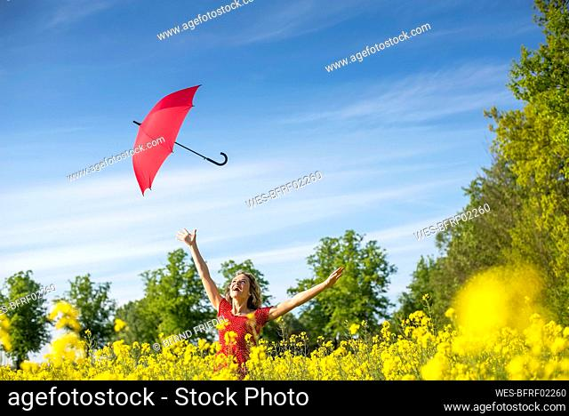 Carefree woman with arms raised throwing umbrella while standing amidst oilseed rapes