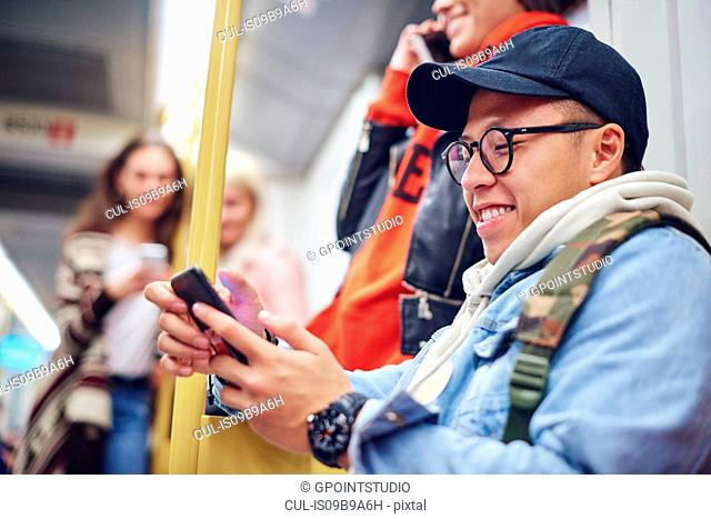 Young man looking at smartphone on city tram