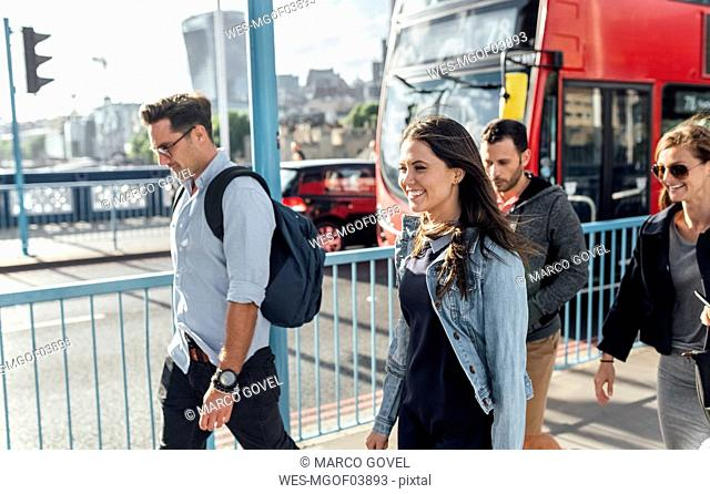 UK, London, happy friends walking on the Tower Bridge