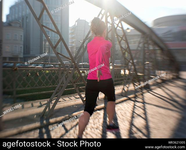 sporty woman running on sidewalk at early morning jogging with city sunrise scene in background