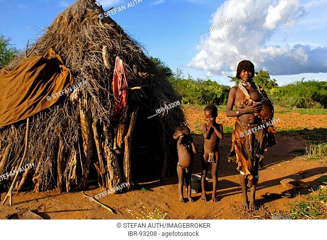 Mother with children and baby on her arm of the Hamar people in front of typical hut in the savannah near Turmi Ethiopia
