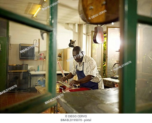 Black lute maker working in workshop