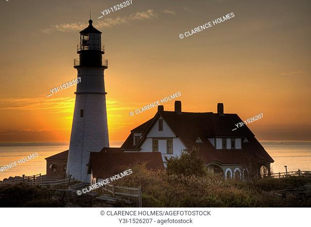 The rising sun behind the Portland Head Light, built in 1791, which protects mariners entering Casco Bay. The lighthouse is located in Fort Williams Park