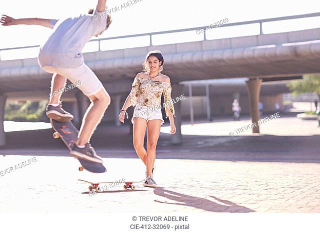 Teenage boy and girl skateboarding at sunny skate park